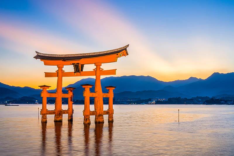 Tramonto con il torii di Miyajima in primo piano durante l'alta marea