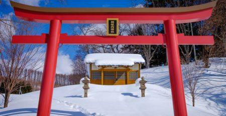 Torii rosso vermiglio immerso nella neve davanti a un piccolo santuario in legno - Watabi