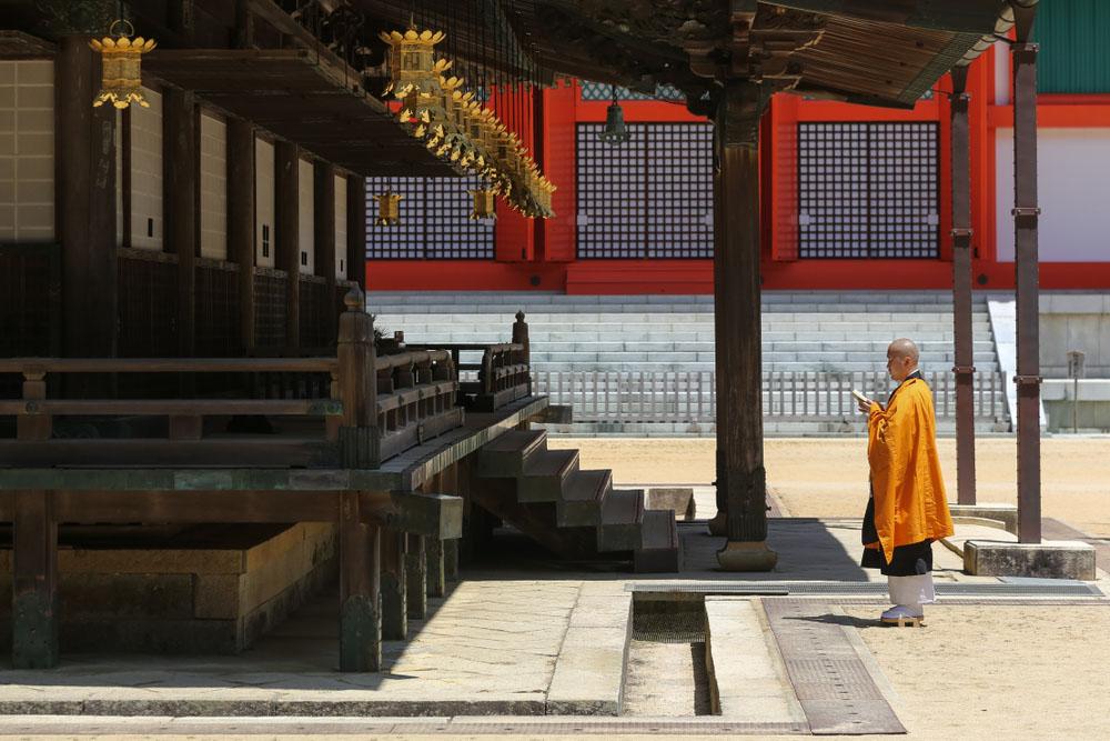 Un monaco in preghiera di fronte a un tempio a Koyasan