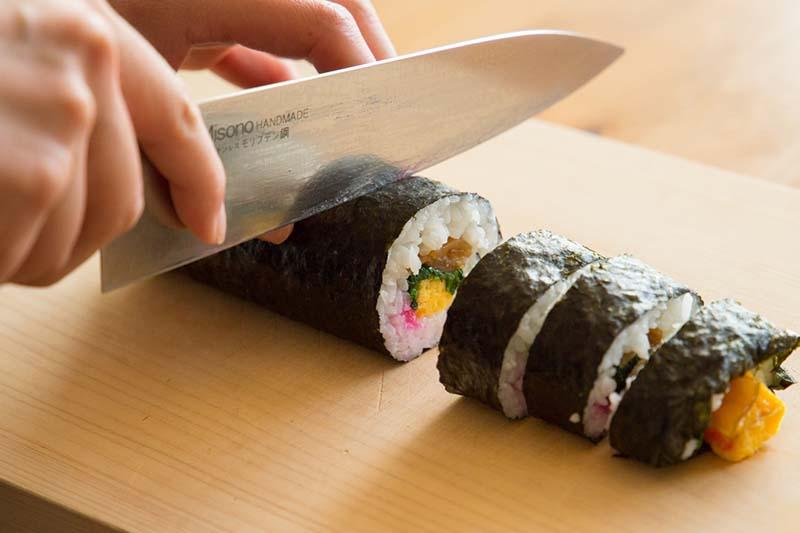 la mano di uno chef mentre taglia dei maki sushi