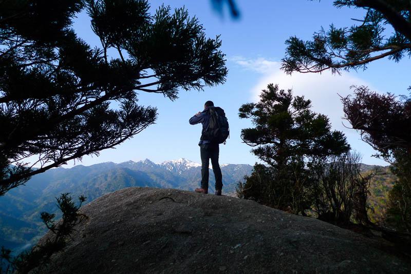 Un viaggiatore fotografa il panorama dalla vetta di un monte.