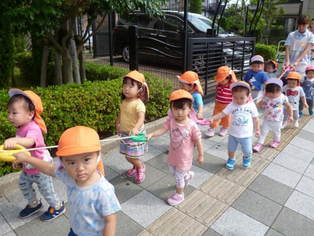 Bambini giapponesi in fila camminano lungo una strada - Watabi